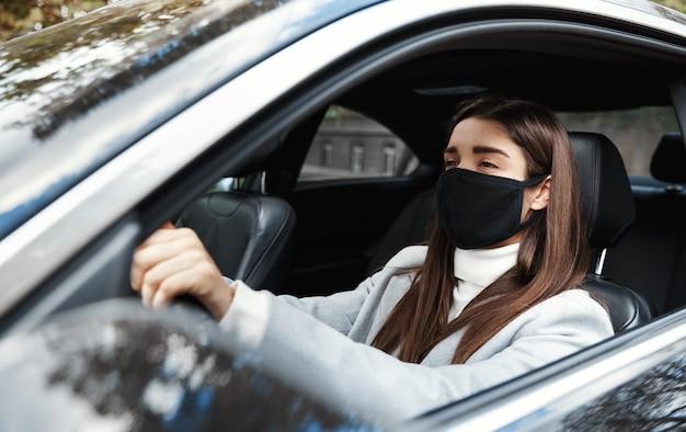 Geschäftsfrau im auto, die gesichtsmaske trägt, die auf ein treffen geht