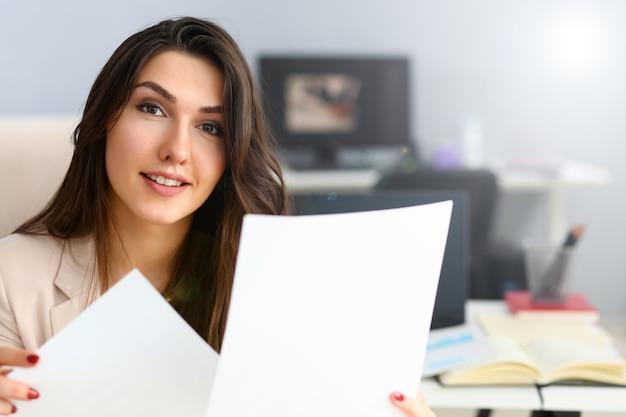 Geschäftsfrau im beige anzug, der dokumente hält