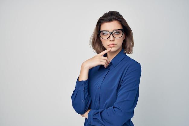 Geschäftsfrau im blauen hemd mit glamour-brille, die hellen hintergrund aufwirft