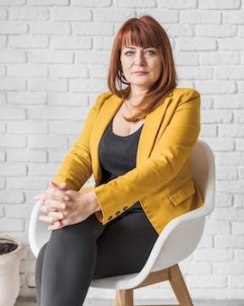 Geschäftsfrau im büro, das auf stuhl sitzt