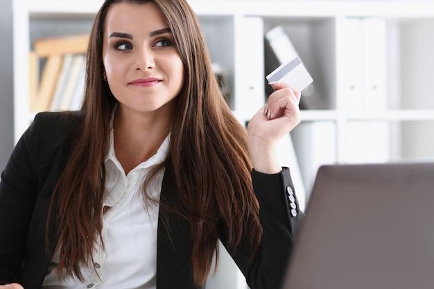 Geschäftsfrau im büro hält eine plastikkredit-debitkarte in der hand, die online-einkäufe im e-commerce des internetshops abwickelt