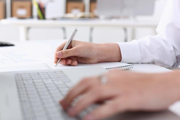 Geschäftsfrau im büro hält ihre hand auf dem laptop. durch finanzielle analyse und berechnung der ausgaben und einnahmen des unternehmens wird ein bericht über die für den berichtszeitraum geleistete arbeit erstellt.