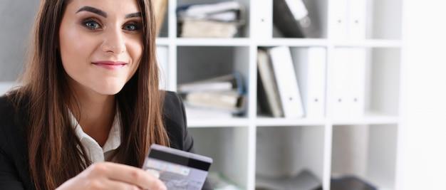 Geschäftsfrau im büro hält plastikkredit