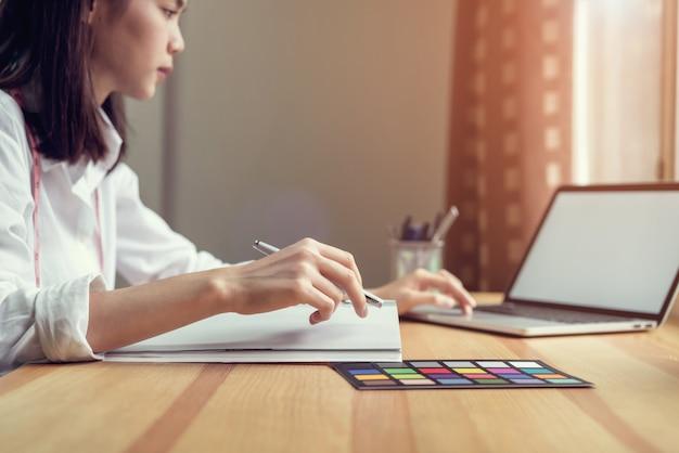 Geschäftsfrau im büro im zufälligen hemd. verwenden sie computer für grafikdesigner.
