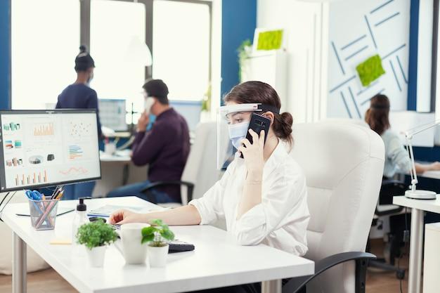 Geschäftsfrau im büro mit gesichtsmaske gegen covid 19, die sich auf dem smartphone unterhält. multiethnische mitarbeiter, die in finanzunternehmen unter wahrung der sozialen distanz arbeiten.