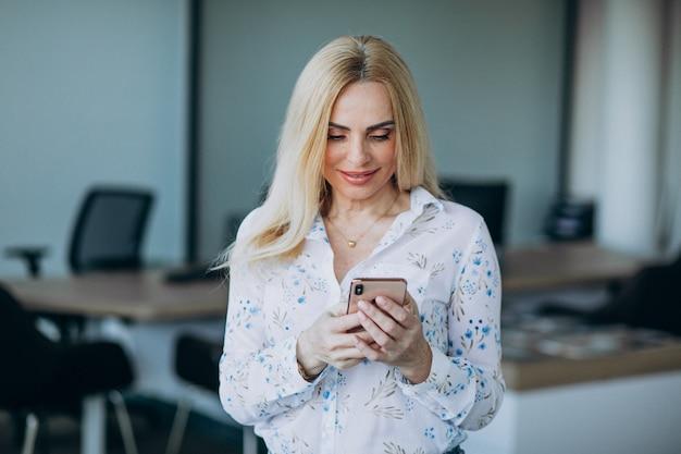 Geschäftsfrau im büro mit telefon