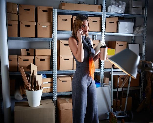 Geschäftsfrau im bürolager mit mobile