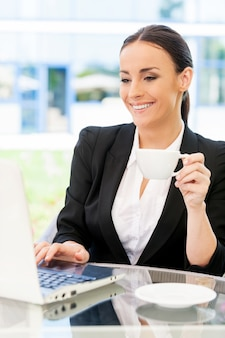 Geschäftsfrau im café. attraktive junge geschäftsfrau in formeller kleidung, die am laptop arbeitet und lächelt, während sie im straßencafé sitzt