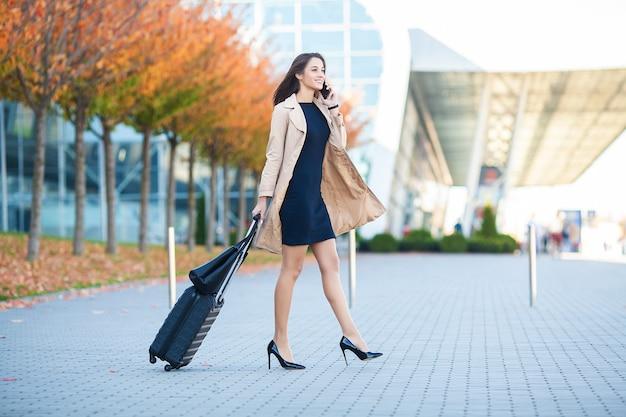 Geschäftsfrau im flughafen, die auf dem smartphone spricht, während mit handgepäck im flughafen geht, das zum tor geht.