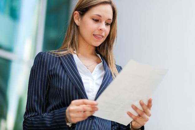 Geschäftsfrau im freien, ein dokument lesend