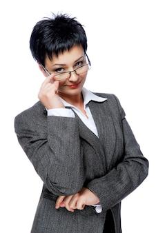 Geschäftsfrau im grauen geschäftsanzug, der von der brille schaut