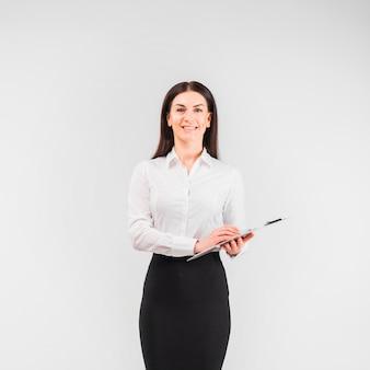 Geschäftsfrau im hemd, das mit klemmbrett steht