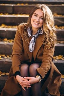 Geschäftsfrau im mantel, der auf der treppe sitzt