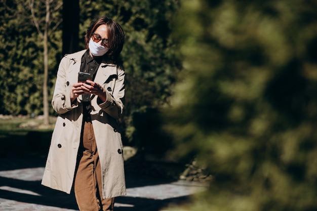 Geschäftsfrau im mantel mit telefon außerhalb