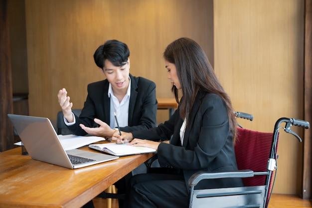 Geschäftsfrau im rollstuhl, die mit ihrem kollegen im büro an einem neuen geschäftsprojekt arbeitet.