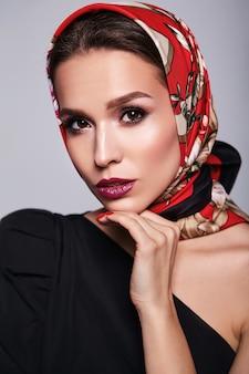 Geschäftsfrau im schwarzen kleid mit abendmake-up und bunten lippen im roten schal