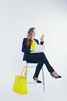 Geschäftsfrau im schwarzen und gelben anzug am telefon sprechen und auf einem laptop arbeiten