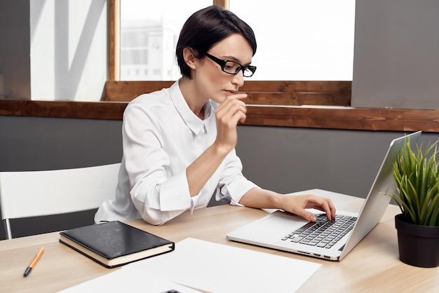 Geschäftsfrau im weißen hemd am arbeitstisch vor laptop-technik