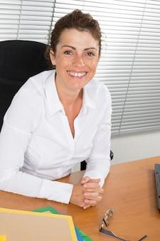 Geschäftsfrau im weißen hemd, das im büro arbeitet