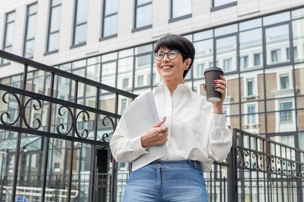 Geschäftsfrau im weißen hemd, das kaffee hält