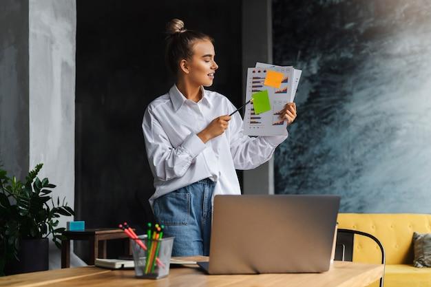 Geschäftsfrau im weißen hemd hält dokumente, kommuniziert durch webkamera.