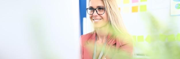 Geschäftsfrau in brille arbeiten am computer am arbeitsplatz und lächeln.