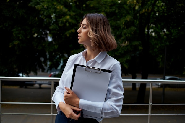 Geschäftsfrau in brillendokumenten arbeitet an der straßenkommunikation. foto in hoher qualität