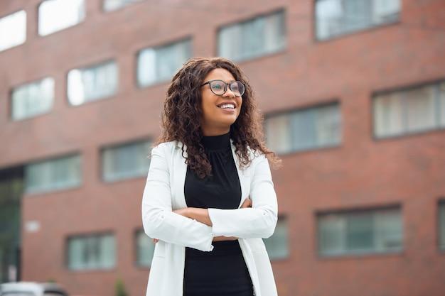 Geschäftsfrau in bürokleidung lächelt, sieht selbstbewusst und glücklich aus