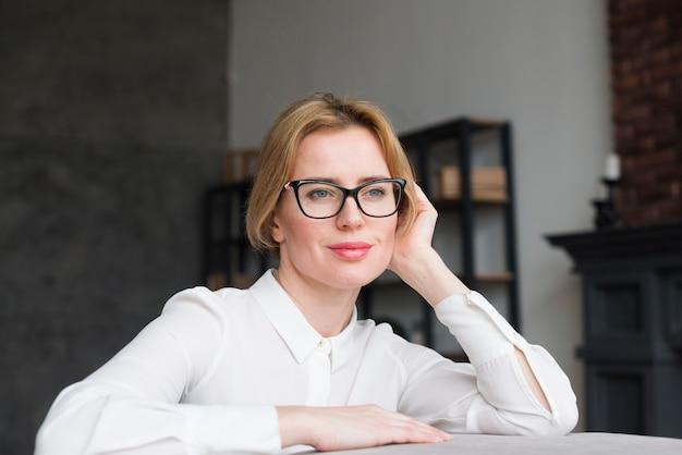 Geschäftsfrau in den gläsern, die auf couch sitzen