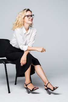 Geschäftsfrau in den gläsern, die auf einem stuhl lokalisiert auf weißer wand sitzen