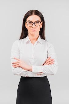 Geschäftsfrau in den gläsern, die mit den gekreuzten armen stehen