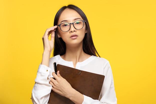 Geschäftsfrau in den gläsern mit notizblock im gelben hintergrund des exekutivsekretärs der hände. hochwertiges foto