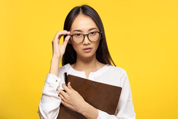 Geschäftsfrau in den gläsern mit notizblock im gelben hintergrund des exekutivsekretärs der hände