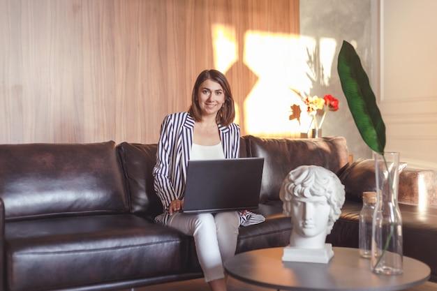Geschäftsfrau in der jacke auf dem ledersofa, das im kreativen kunstbüro arbeitet