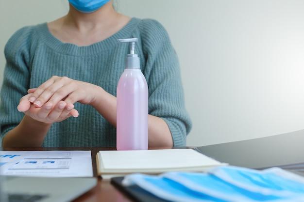 Geschäftsfrau in der maske, die hände durch alkoholdesinfektionsmittel oder alkoholgel von pumpflasche wäscht