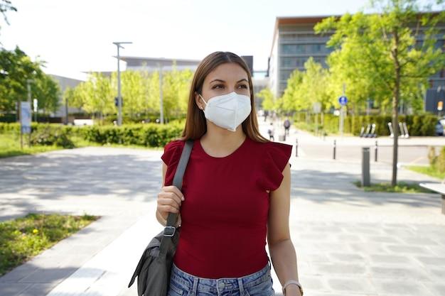 Geschäftsfrau in der modernen stadtstraße mit kn95 ffp2-schutzmaske, die zur seite schaut