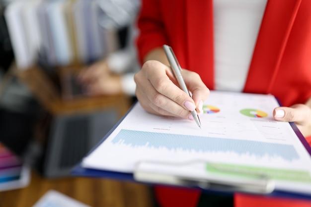 Geschäftsfrau in der roten jacke hält zwischenablage mit dokumenten und stift nahaufnahme. pflege des personaldokumentationskonzepts.