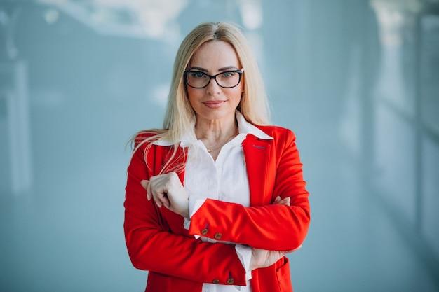 Geschäftsfrau in der roten jacke lokalisiert im büro