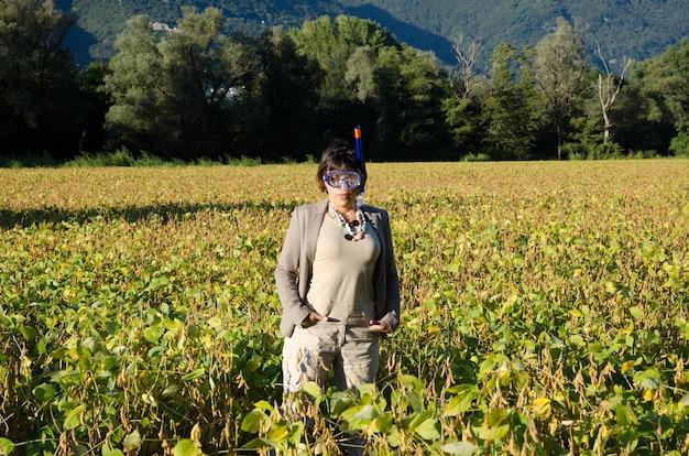 Geschäftsfrau in einem anzug, der im feld mit einer tauchmaske steht
