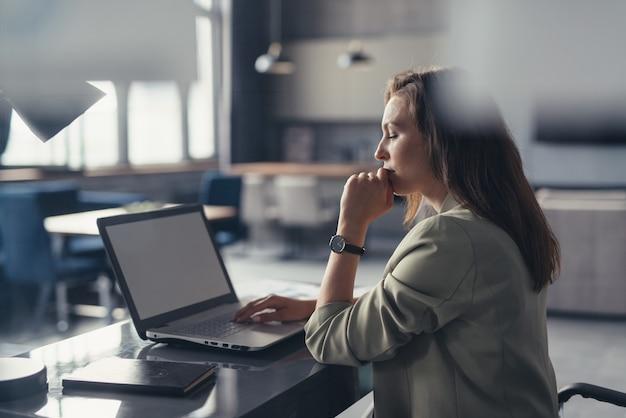 Geschäftsfrau in einem anzug, der mit einem laptop an ihrem schreibtisch in ihrem hauptbüro arbeitet.