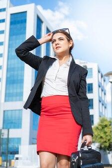 Geschäftsfrau in einem anzug gekleidet in ihrem arbeitsbereich erfolgreiche junge berufstätige frau