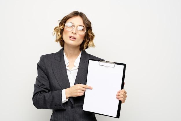 Geschäftsfrau in einem anzug und in den gläsern, die im studio, heller hintergrund aufwerfen