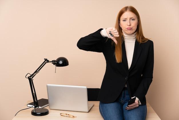 Geschäftsfrau in einem büro, das daumen nach unten zeigt