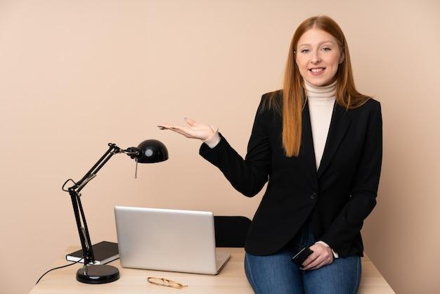 Geschäftsfrau in einem büro, das imaginären copyspace auf der handfläche hält