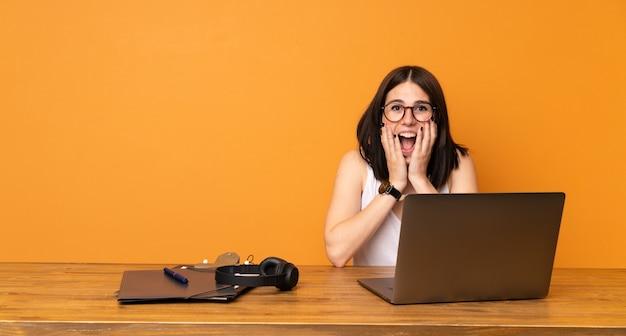 Geschäftsfrau in einem büro mit überraschung und entsetztem gesichtsausdruck