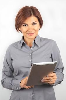 Geschäftsfrau in einem hemd und einem tablet in ihren händen