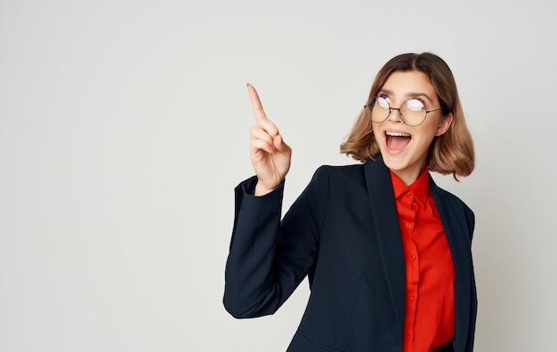 Geschäftsfrau in einem klassischen blauen anzug und einem roten hemd gestikuliert