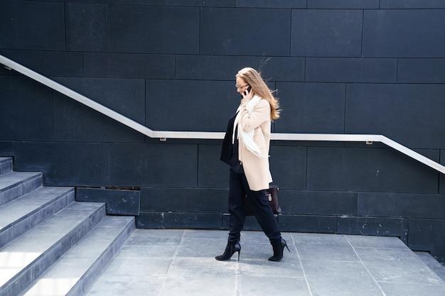 Geschäftsfrau in einem mantel mit einer tasche in den händen geht die stufen zum gebäude hinauf. das konzept von karriere und business