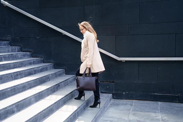 Geschäftsfrau in einem mantel mit einer tasche in den händen geht die stufen zum gebäude hinauf.