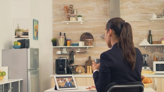 Geschäftsfrau in einem videoanruf mit ihrem vater während ihres vaters beim frühstück. mit moderner online-internet-webtechnologie über eine webcam-videokonferenz-app mit verwandten, familie, freunden chatten